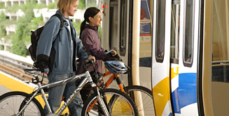 two_people_with_bikes_at_skytrain_station_index_lg_version